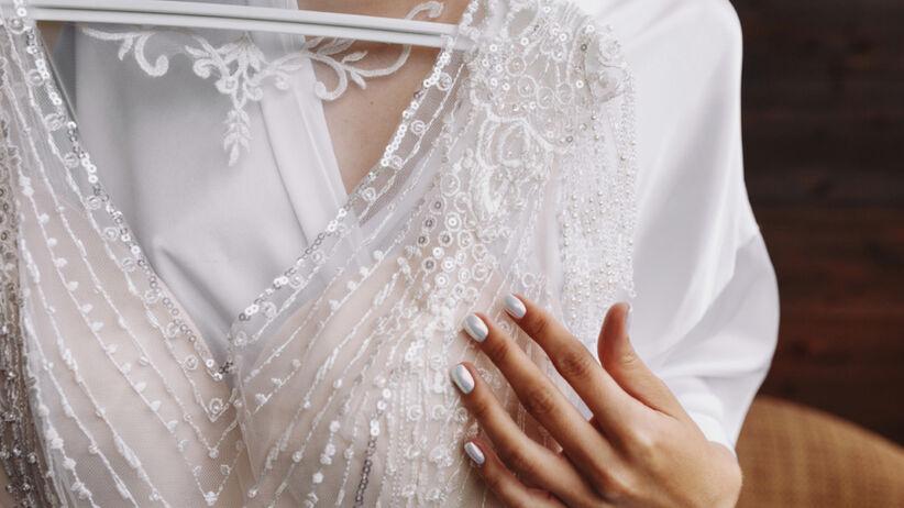 Panna młoda w aksamitnym szlafroku przymierza do siebie suknię ślubną