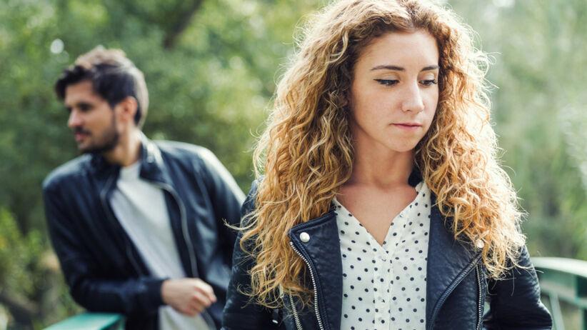 Smutna kobieta odchodzi od degradującego ją partnera