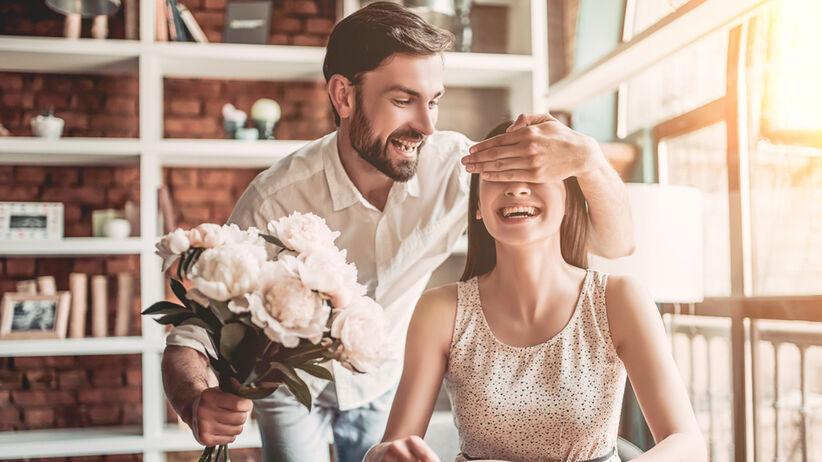 Szczęśliwa para znajduje się w jadalni, mężczyzna zasłonił kobiecie oczy, kupił dla niej kwiaty