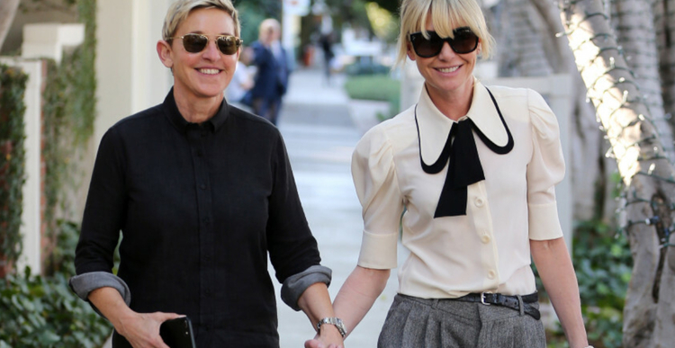 Ellen DeGeneres w czarnym stroju i jej żona Potia De Rossi w białej koszuli idą po ulicy trzymając się za ręce
