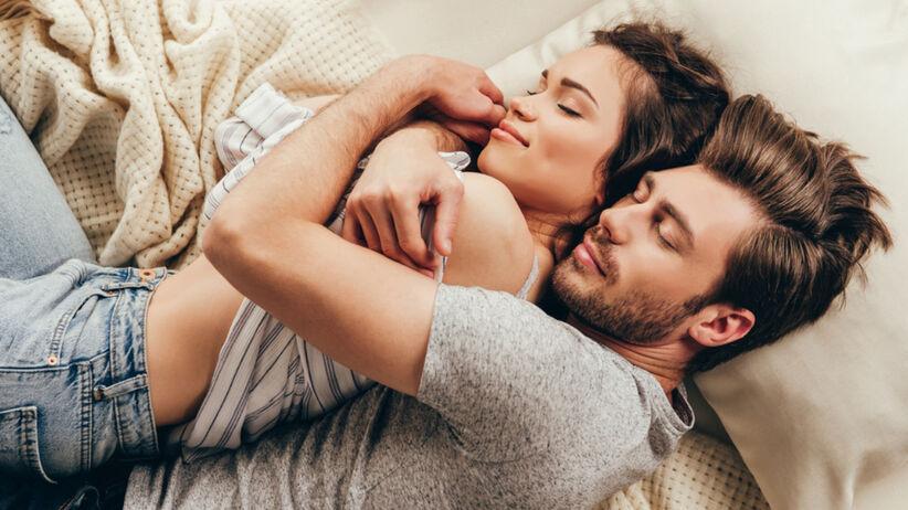 Para zakochanych śpi przytulając się na łóżku