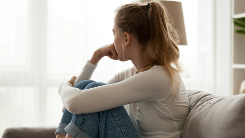 Zasmucona dziewczyna siedzi samotna wpatrzona w okno