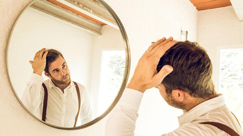 Mężczyzna z kompleksami przegląda się w lustrze