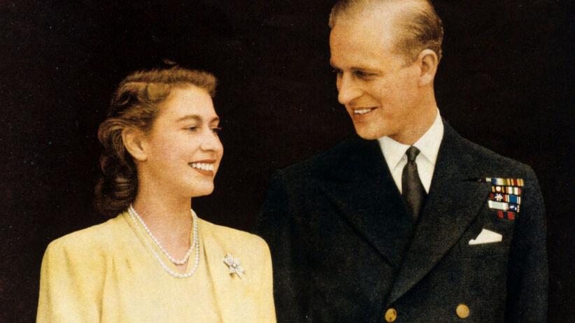 Królowa Elżbieta jako księżniczka w żółtej sukience i książę Filip w mundurze podczas ogłoszenia ich zaręczyn