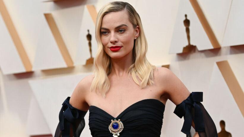 Margot Robbie w czarnej sukni i z czerwoną szminką na ustach na czerwonym dywanie przed galą rozdania Oscarów