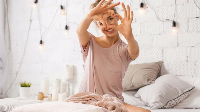 Zakochana kobieta siedzi na łóżku i pokazuje serduszko