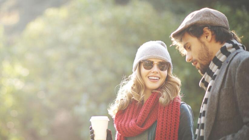 Pierwsza randka, para idzie po parku z kawą i rozmawia