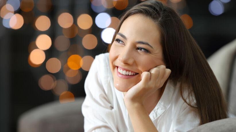 Uśmiechnięta singielka w białej bluzce leży na kanapie na tle świątecznych lampek