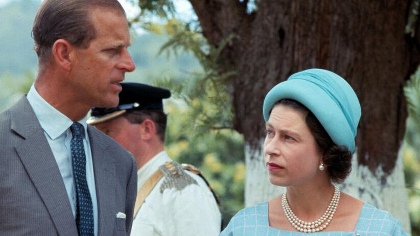 Książę Filip w szarym garniturze i królowa Elżbieta w niebieskim kostiumie i kapeluszu dyskutują