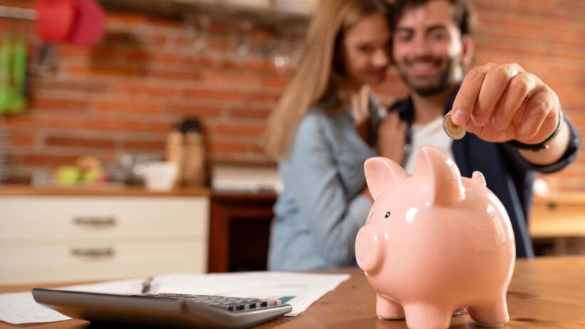 Para wrzuca oszczędności do świnki skarbonki
