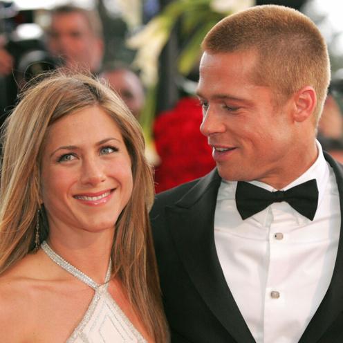 Jennifer Aniston w białej sukience i wpatrzony w nią Brad Pitt w czarnym smokingu na czerwonym dywanie w Cannes