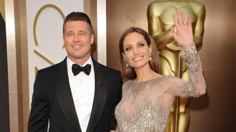 Angelina Jolie w złotej sukni i Brad Pitt w smokingu i muszce na czerwonym dywanie przed galą rozdania Oscarów