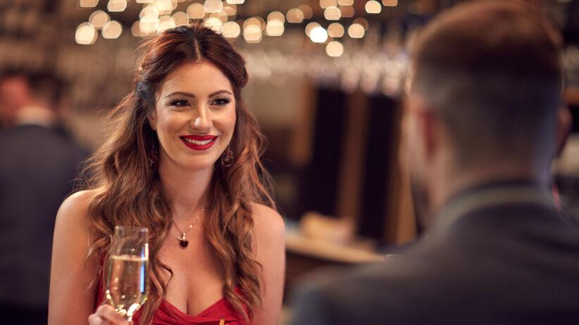 Pewna siebie kobieta w czerwieni siedzi na randce z mężczyzną