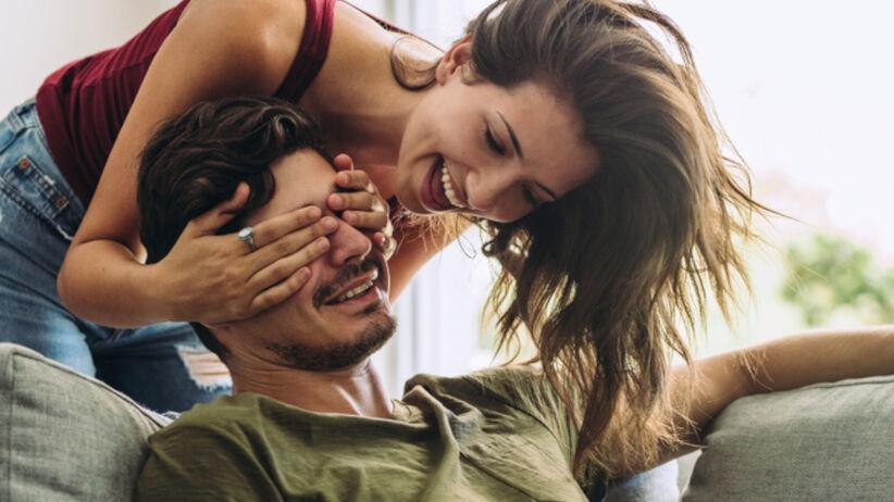 Szczęśliwa kobieta i zirytowany mężczyzna we wspólnym mieszkaniu