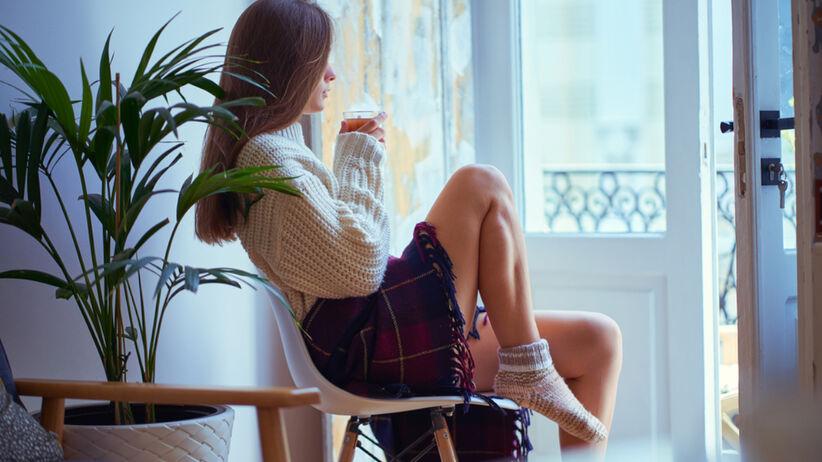 Smutna kobieta siedzi na krześle z kubkiem herbaty i wygląda przez okno