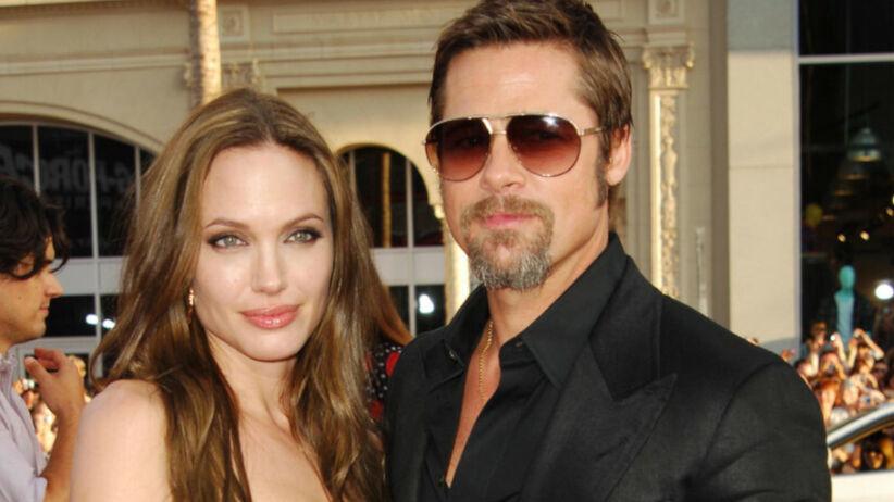 Angelina Jolie w skórzanej sukience i Brad Pitt z brodą w czarnym garniturze i okularach przeciwsłonecznych na czerwonym dywanie