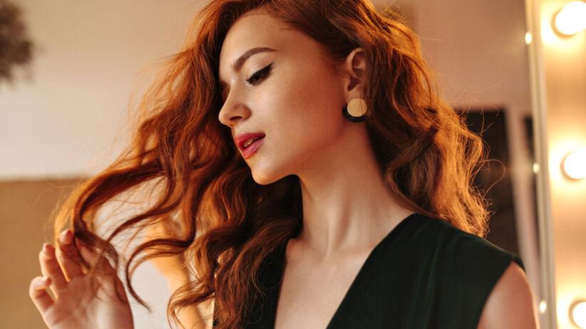 Kobieta o rudym kolorze włosów stoi przed lustrem i obserwuje swoje kosmyki